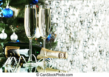 Glasses of champagne with bottle on a lights background