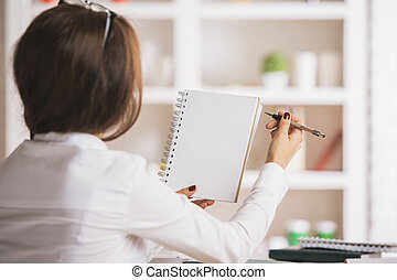 Woman writing in notepad - Back view of young woman holding...