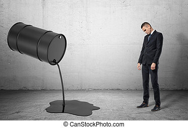Inclined barrel with black liquid oil pouring out of it on and dissapointed sad businessman