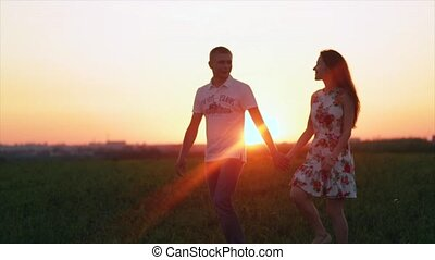 Loving couple walking at sunset in field holding hands, hugging, kissing