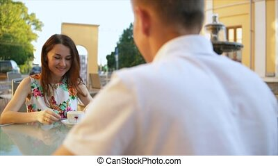 Loving couple sitting at a table in an open-air restaurant.