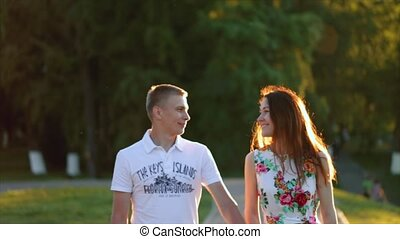 Young beautiful sensual couple walking at sunset looking into each others eyes