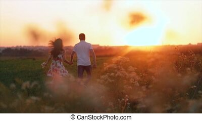 Young pair of runs in the sunset, the man picks up the girl and turns around