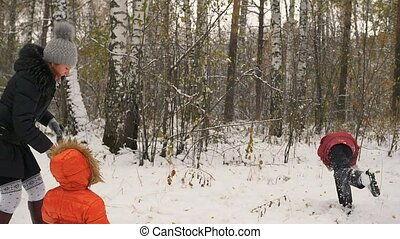 family playing by throwing snowballs in the winter Park -...
