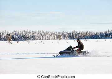 Man driving snowmobile in Finland - Man driving sports...