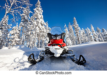 Snowmobile in snowy Finland - Red snowmobile in Finnish...
