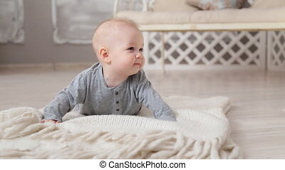 Happy cute little baby - cute little boy sitting on the...