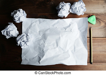 Crumpled up papers with a sheet of blank paper and a pencil...