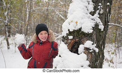 kid playing throwing snowballs from behind tree in winter...
