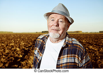 black earth - An elderly farmer standing in a plowed field....