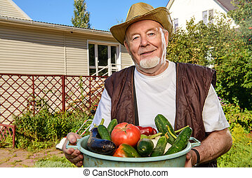 countryside life - Smiling senior man with his harvest in...