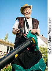 leaf blower - Autumn in a garden. Senior man removes fallen...