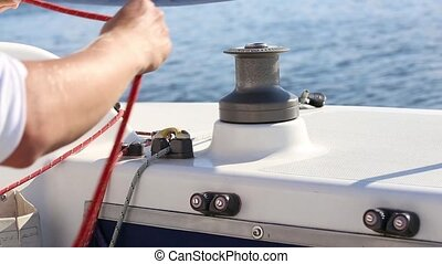 Sailor and winch on yacht - Sailing crew member on sailboat...