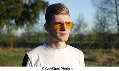 Handsome young man takes off sunglasses and enjoying the sun