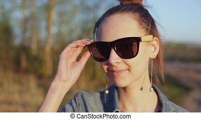 Young, stylish, informal girl looks around, takes off...