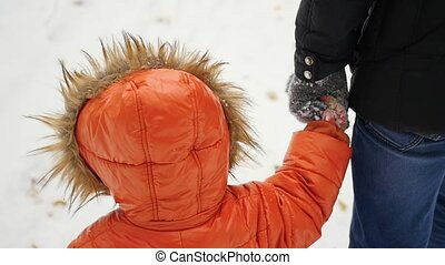 a child walks holding the hand of an adult in the winter...