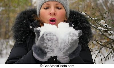 girl blows snow with hands closeup in slowmo