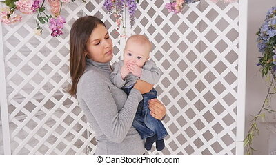 Young mother is holding her little baby in room