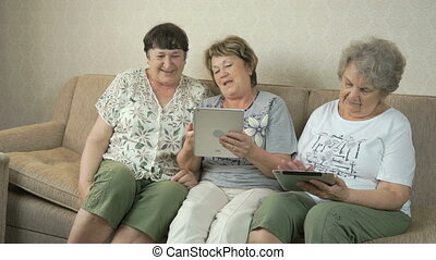 Elderly women look at photos on screen of tablets - Elderly...