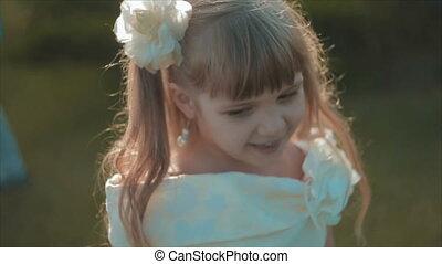 Little Girl in White Spinning Around Herself