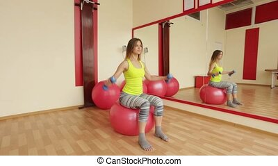 Young girls trainers biceps using dumbbells while sitting on a fitball.