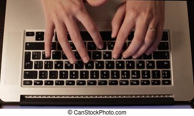 Female hands with a ring typing text on a keybordy, the view...
