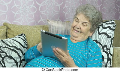 Old woman holds a tablet computer indoors