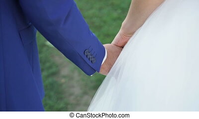 Bride and groom holding hands during walking