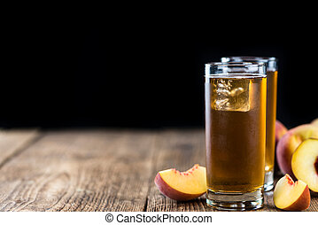 Ice Tea (Peach) on an old wooden table (selective focus;...