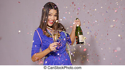 Sexy young woman celebrating New Year with a bottle and...