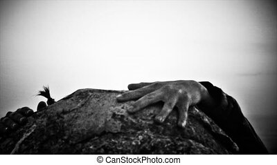 Young man with little tail on hair hardly climb on big rock...