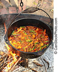 Hobo Stew Cooked over an Open Fire - Hobo stew is cooked in...