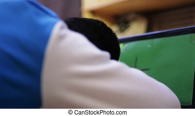 Young brunette boy in blue sport jacket fall asleep in front screen of computer. Tiredness. Teenager