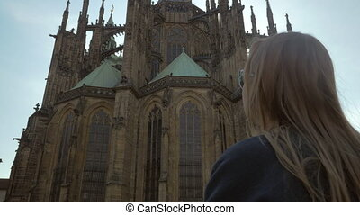 Woman tourist taking mobile photo of St. Vitus Cathedral,...