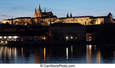 Timelapse of ships on river near Prague Castle at night -...