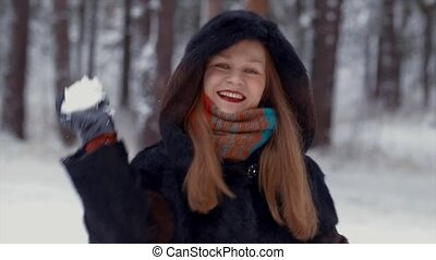 Beautiful girl smiling flirting and playing snowballs.