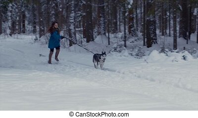 Girl runs with her dog Husky in a winter forest