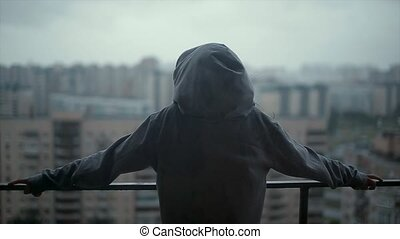girl standing on the balcony in the rain view from the back