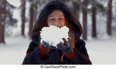 Winter lady blowing a handful of snow right in the camera
