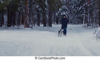 Man runs with the dog Husky in a winter forest towards the camera