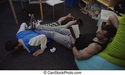 Muscle man read book on beanbag keep legs on boy try to press up from floor but fall. Sport exercise