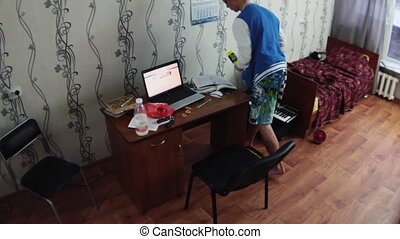 Boy try juggle bottles in dormitory room. Notebook, bottle...