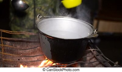 man cooking food in a pot on the fire, tourist outdoor recreation outdoors