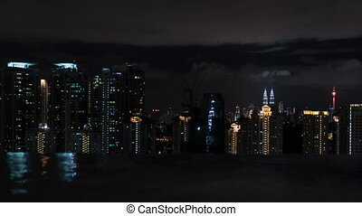 Timelapse of night Kuala Lumpur, view from rooftop pool -...