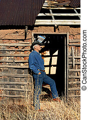 Abandoned and Empty Adobe - Man leans against dilapidated...
