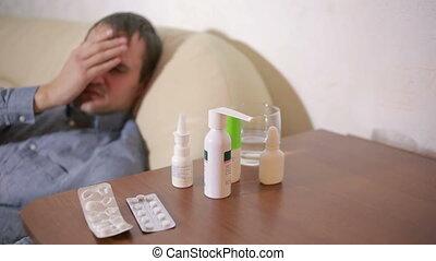 sick man lying in bed suffering virus having medicine tablets. drinking pill