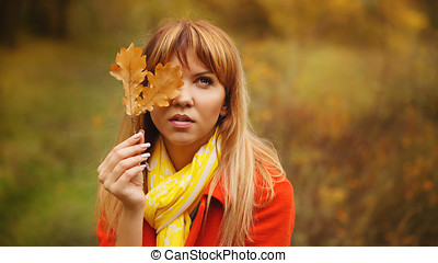 Woman hides her face behind the leaf