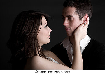 Young Couple Embracing against Dark Background