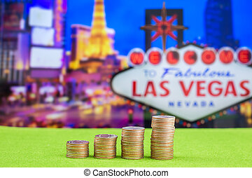 Stack of coins with blur Las vegas sign on background