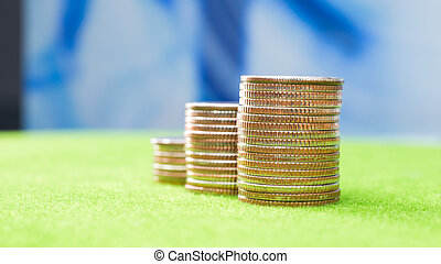 Stack of coins on green grass